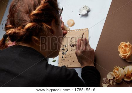 Redhead woman writing love word on craft paper with roses buds on table