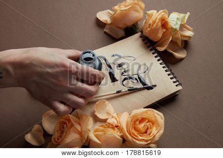 Female hand writing love word on craft paper, roses around