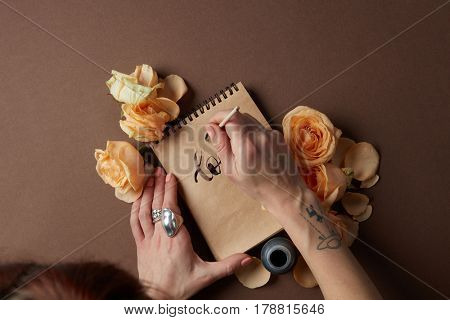 View frome above of woman writing on paper with brush