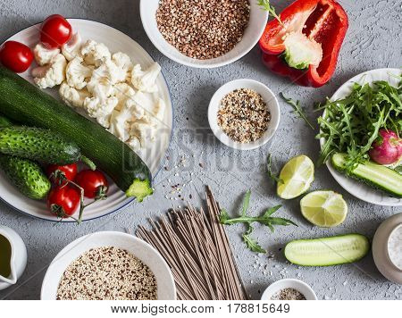 Vegetarian food set. Zucchini cauliflower sweet pepper soba noodles quinoa buckwheat - healthy vegetarian food. On a gray background top view