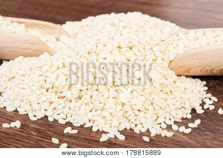 Heap Of Sesame Seeds With Wooden Scoop On Board