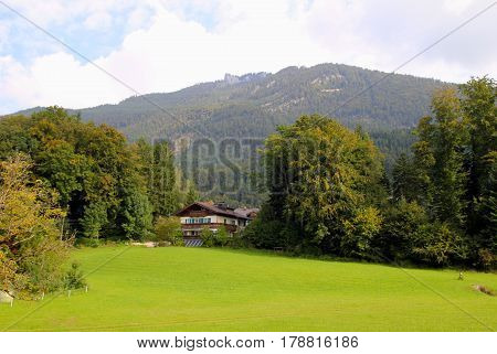 Travel To Sankt-wolfgang, Austria. The View On The Green Meadow With The Houses And The Mountains On