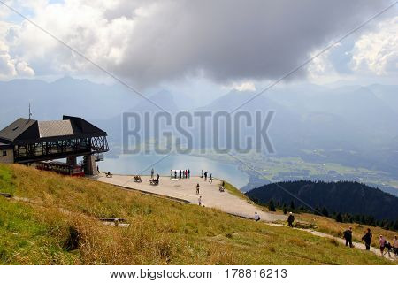 Travel To Sankt-wolfgang, Austria. The View On The Mountains And A Lake With The Walking People.