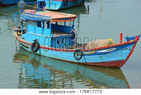 Fishing boat with a coracle boat stored on deck. Close-up of colorful blue boat with red trim. Reflection in water. Fishing is an important industry in Vietnam Asia.  The harbor is a popular tourist site. Horizontal. No people. Photography.