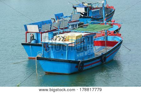 Fishing boats in harbor.  Three traditional colorful blue boats with red and black trim. Fishing is an important industry in Vietnam Asia.  The Nha Trang harbor is a popular tourist site. Horizontal. No people. Photography. Copy space.
