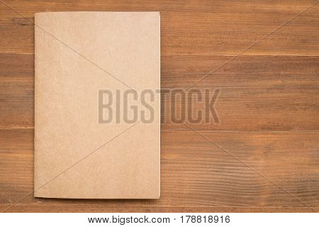 blank brown book cover on wooden background