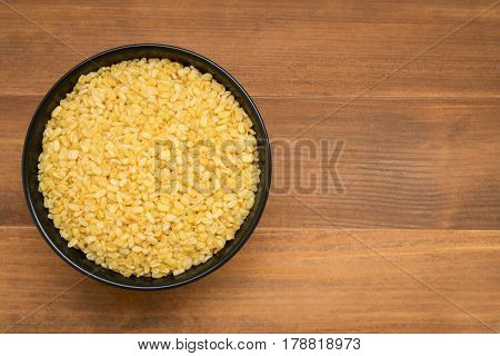 top view of roasted hulled split mung bean in black bowl on brown wooden background