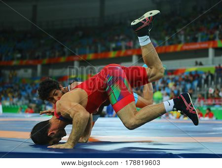 RIO DE JANEIRO, BRAZIL - AUGUST 14, 2016: Wrestlers Elvin Mursaliyev of Azerbaijan  (in red) and Mahmoud Fawzy of Egypt in action during Men's Greco-Roman 75 kg Qualification of the Rio 2016 Olympics
