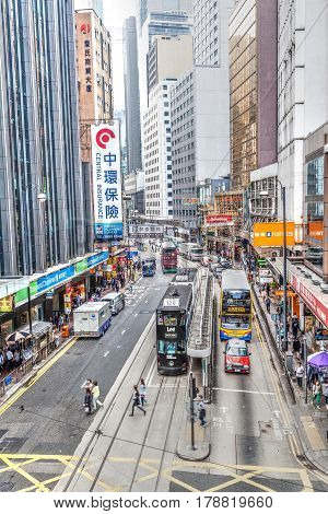 Hong Kong China - March 31 2015: Historic double-decker trams share the road with other traffic vehicles in the busy downtown Central District of Hong Kong Island. The area bustles with shoppers and tourists because of its many restaurants and fashion bou