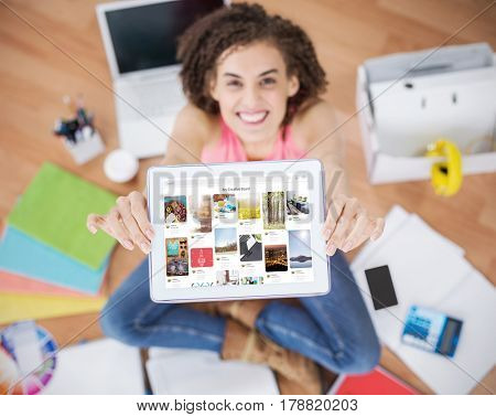 Composite image of website page against young creative businesswoman showing her tablet