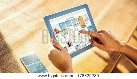 Composite image of website page against over shoulder view of casual man using tablet