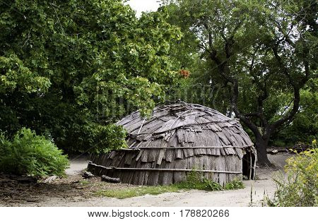 Plimoth Plantation, Plymouth, Massachusetts - September 10, 2014 - Wide view of a Wampanoag Indian hut made of branches and covered in bark in the Wampanoag Indian Village at Plimoth Plantation, Plymouth, Massachusetts surrounded by trees and foliage