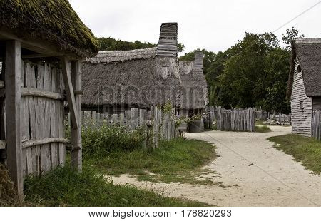 Plimoth Plantation, Plymouth, Massachusetts - September 10, 2014 - Wide shot of a path through some of the thatched cottages old gray fences in the Pilgrim Settlement at Plimoth Plantation, Plymouth, Massachusetts surrounded by trees and foliage