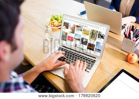 Composite image of website page against overhead view of a man using laptop