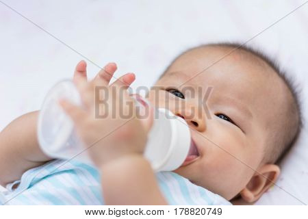 Smiling Asian Baby Infant Enjoy Drinking Water From Bottle