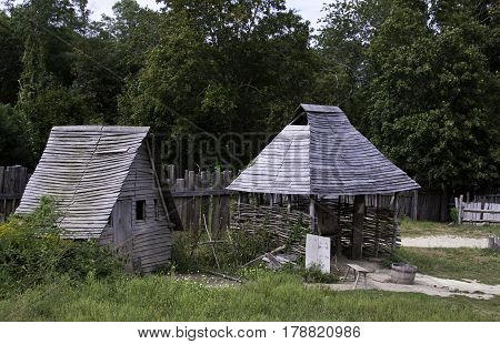Plimoth Plantation, Plymouth, Massachusetts - September 10, 2014 - Wide view of an old gray wooden shed beside an old wood roofed kiln in the pilgrim village at Plimoth Plantation, Plymouth, Massachusetts with trees and foliage