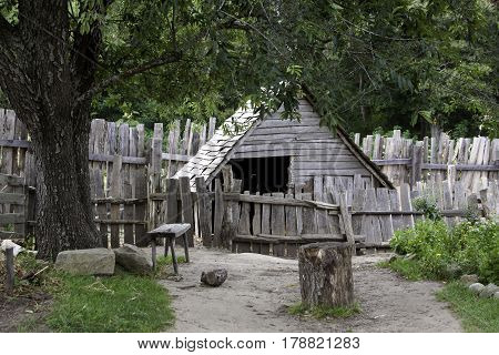 Plimoth Plantation, Plymouth, Massachusetts - September 10, 2014 - Wide view of a path leading to an old gray wooden shed beside with a rickety old fence in the pilgrim village at Plimoth Plantation, Plymouth, Massachusetts with trees and foliage