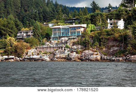A village on a rocky beach in the  Strait of Georgia in West Vancouver  British Columbia, a coastline and a forest.