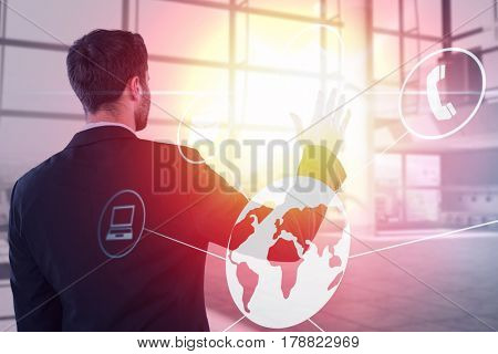 Businessman pretending to touch invisible screen against interior of empty office 3d