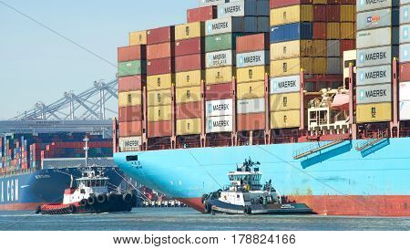 Oakland CA - March 14 2017: Tugboats are powerful for their size and strongly built. Tugboats Z-THREE and VALOR assisting cargo ship CRETE MAERSK to maneuver into the Port of Oakland.