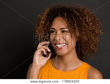 Beautiful African American woman making a phone call and laughing