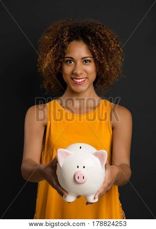 Portrait of a beautiful African American woman holding a Piggybank