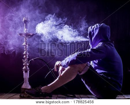 A Man Smokes A Hookah On A Black Background, Beautiful Lighting