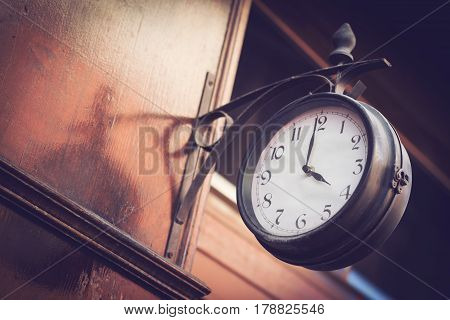 horizontal side view of a vintage outdoor clock on a wooden wall by the entrance of a restaurant selective focus