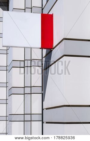 vertical side view of empty white square signage on the exterior of a building