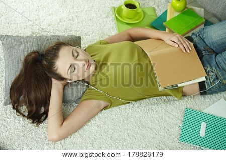Young female student takes a nap during studying, lying on the floor. High angle view.