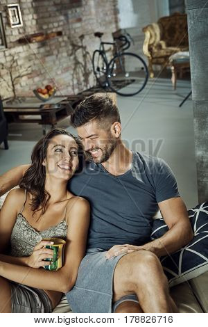 Happy loving couple resting at trendy home on sofa, smiling.