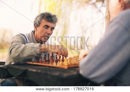Active retired people old friends and free time two senior men having fun and playing chess at park