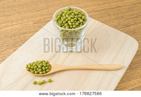 Cuisine and Food Raw and Uncooked Mung Dried Beans in A Wooden Spoon and A Tumbler on A Wooden Cutting Board.