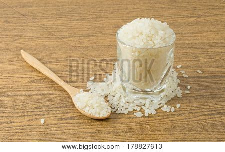Japanese Cuisine Raw and Uncooked Japanese Rice in A Wooden Spoon and A Tumbler.