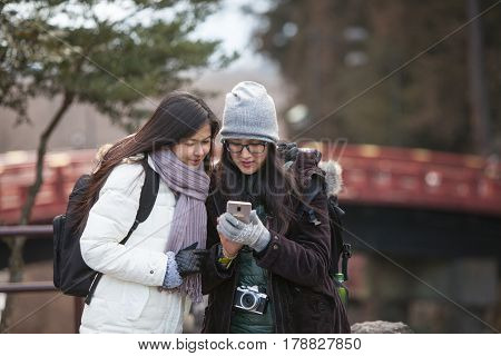 Two woman backpacker see picture in smartphone screen with red bridge background