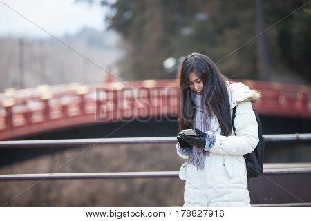 Woman traveler use her smartphone background red bridge