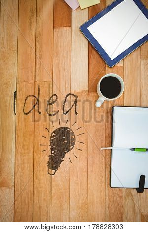 Close-up of glowing bulb against business desk with tablet and coffee