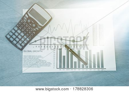 Graph with calculator and pen on wooden table