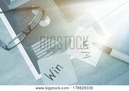 Win written on sticky note with marker spectacles and graph on wooden table