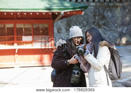Two woman backpacker see picture in camera screen