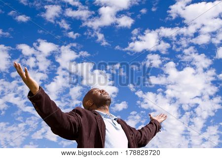 African American man with open arms and clouds in the background.