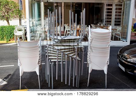 A pile of stacked chairs in front of a street cafe