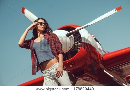 Pilot woman next to propeller plane outdoors in sunny day. Attractive young multi-racial Asian Caucasian sexy girl in jeans and shirt standing at sport airplane in airport.