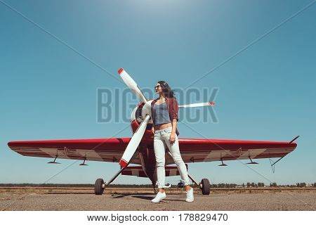 Pilot woman next to propeller plane outdoors in sunny day. Attractive young multi-racial Asian Caucasian sexy girl in jeans shirt and sunglasses standing in full length at sport airplane in airport.