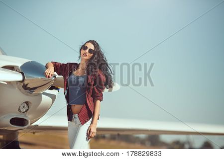Pilot woman next to propeller of small private business plane outdoors in sunny day. Attractive young multi-racial Asian Caucasian sexy girl in jeans and shirt standing at sport airplane in airport.
