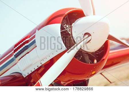 Sport airplane red and white propeller closeup outdoors on the meadow