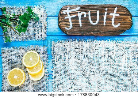 Background of narrow wood planks painted in blue. Bunch of blooming apple tree and young black current twigs. Lemons in the corner. Wood signboard with text 'Fruit' as title bar