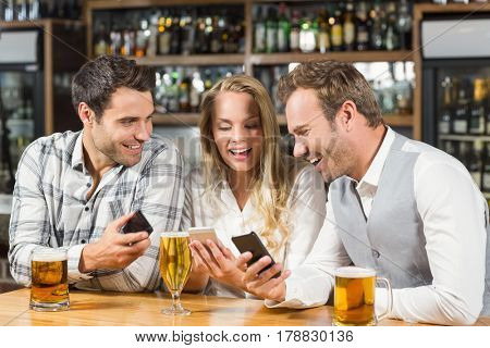 Attractive friends smiling while looking at their smart phones in a bar