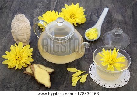 Chrysanthemum herb flower tea with glass teapot and cup with lid, ginger spice and stone buddha head. Also used in traditional chinese and japanese herbal medicine.