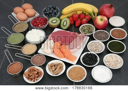 Health food for body builders with lean meat, salmon, dairy, fruit, supplement powders, herbs, pulses, nuts, cereals and seeds on slate background.